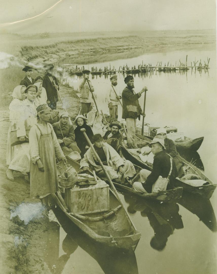 Участники экспедиции с группой крестьян на берегу реки.