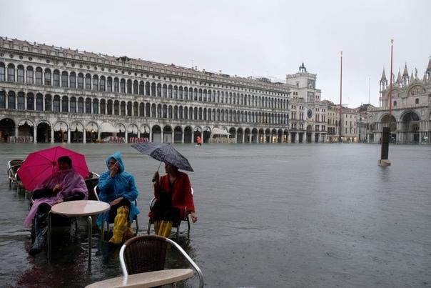 Туристы отдыхают на затопленной площади Сан-Марко в период сезонного половодья, Венеция