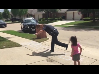 Police officer takes time on his lunch break to play hopscotch with a young girl