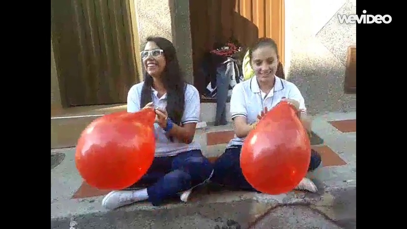 2 Girls blow up a red balloon to see who can pop it first
