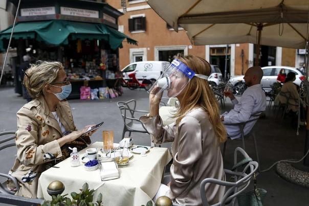 Женщина пьет кофе в римской кофейне, которая открылась после двухмесячного локдауна Cecilia Fabiano/AP